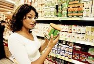 una donna al supermercato controlla l´etichetta di un prodotto