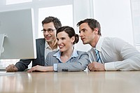 Business people in front of computer, smiling