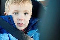 Young boy wearing car seatbelt