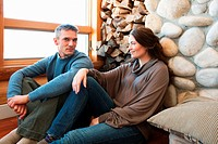 Mid adult couple sitting in log cabin