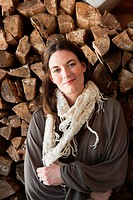 Woman in front of logs, portrait (thumbnail)