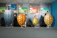 Four friends standing behind sea turtle shells