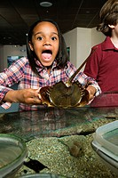 Surprised girl holding ray fish in aquarium
