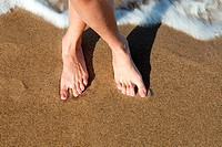 Woman's bare feet on sandy beach