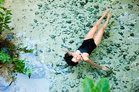 Young woman floating in lagoon, Grande Cenote, Quintana Roo, Tulum, Mexico
