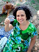 Woman toasts to camera at vegan picnic.
