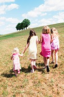 Four girls walking in field