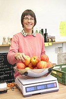 Woman weighing organic apples in farm shop