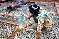 Welder in protective mask welding metal construction on open air.