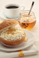 Halved roll with cottage cheese and honey for breakfast