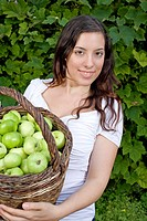young woman holding a basket of apples