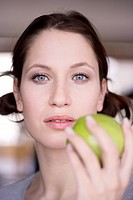 Young woman holding green apple, close_up, portrait