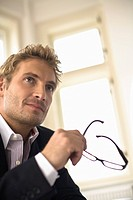 Businessman holding glasses, close_up