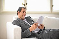 Businessman reading document, smiling