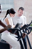 Three popele biking at health club, focus on girl and perosnal trainer