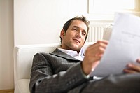 Businessman lying on sofa, reading document