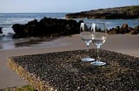 Glasses on a table beside beach, Playa de Toro, Llanes, Asturias, Spain