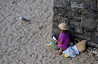 Woman reading on the beach of Ribadesella, Asturias, Spain