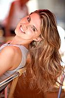 Germany, Lower_Bavaria, Landshut, Close up of young woman sitting at street cafe, smiling, portrait