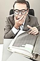 Close up of mature businessman yawning in office