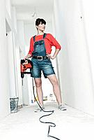 Germany, Cologne, Young woman with electric drill for renovation in corridor