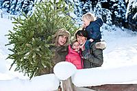 Austria, Salzburg Country, Flachau, View of family with christmas tree in snow