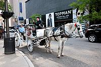 A couple on a horse drawn carriage in the city  The driver wears a top hat as does the passenger A sign for 'Topman' is in the backdround