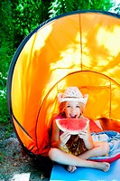 Camping children girl in tent eating watermelon slice fruit in outdoor forest