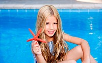 children blond girl in summer vacation pool with starfish