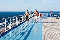 Two men running on jogging track on the sports deck of Carnival's Triumph cruise ship in the Gulf of Mexico