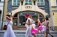 women having fun in front of facade of Draakoli gallery,in 18 Pikk street,Tallinn,Estonia