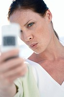 Close_up of a mid adult woman looking at a mobile phone