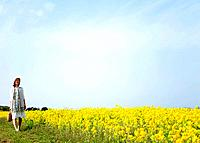 Young woman walking next to oilseed rape field