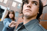Close_up of a young man looking serious with a young woman reaching for him