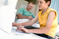 Close_up of a boy using a laptop with his father sitting in the background