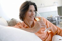 Mature woman listening to music and holding a champagne flute