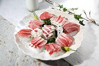 Sliced raw tuna on plate, high angle view, differential focus