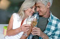 Mature couple sitting on the bed and toasting with champagne
