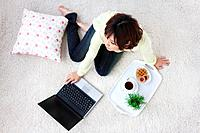 Young woman sitting on carpet, using laptop