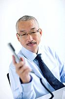 Businessman holding phone receiver, white background