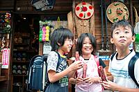 Kids in front of Dagashi_ya eating snacks, Japan