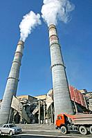 Cement factory smokestacks. Cement is made by heating limestone with other materials in a kiln, then grinding the residue with a small amount of gypsu...