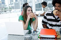 Close_up of a young couple sitting in front of a laptop and eating burgers