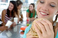 Close_up of a young woman holding a burger and smiling