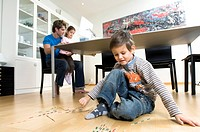 Close_up of a boy sitting on the floor with his sister and father using a computer in the background