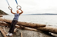 A woman performs suspension training exercises on a rustic beach.