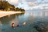 Woman relaxing in a lagoon at sunset, Rarotonga, Cook Islands.