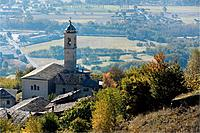Aerial view of village stone church with bell tower, slate roofs, and autumn colours of trees, with plain below of planted fields, Lombardy, Italy