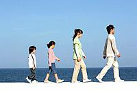 Family walking single file along the beach