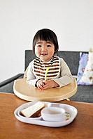 Portrait of baby boy sitting in high chair, smiling